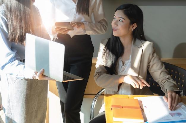 Le giovani donne di affari discutono la strategia dei grafici e il programma finanziario