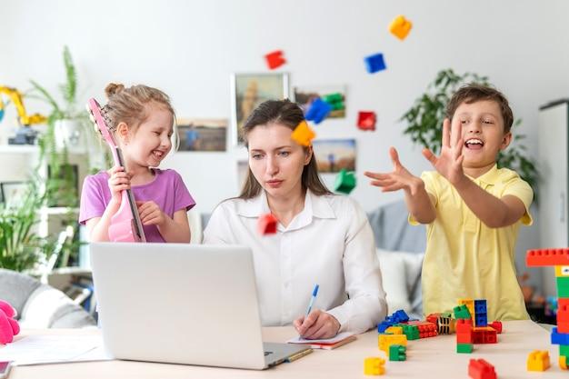 Le giovani donne lavorano a casa con il laptop, insieme ai bambini. i bambini fanno rumore