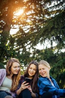 Le giovani donne si siedono sull'erba verde tra gli alberi e guardano nello smartphone