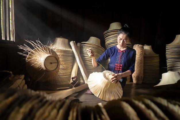 Le giovani donne stanno tessendo nel canestro fatto a mano del campo della tailandia.