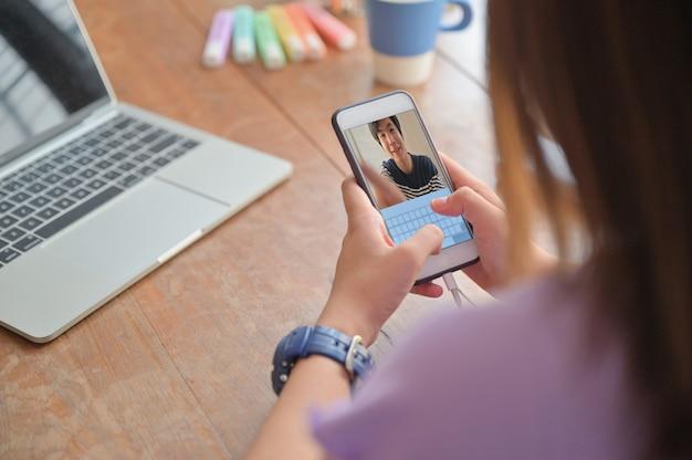 Le giovani donne usano lo smartphone per le videochiamate con un amico maschio