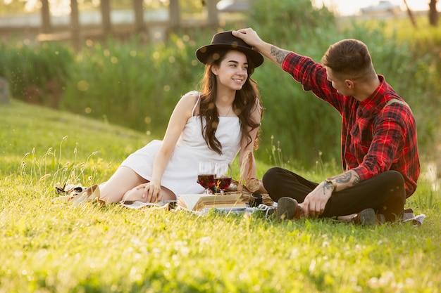 Le giovani e coppie felici che godono di un picnic si sono sparse sul parco nel giorno di estate