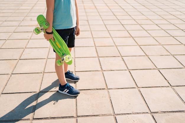 Le giovani gambe della scuola boy cool camminano con penny board nelle mani