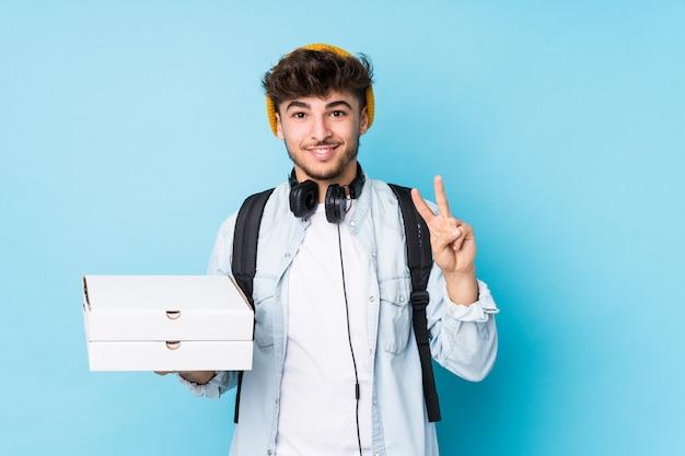 Le giovani pizze arabe della tenuta dell'uomo dello studente hanno isolato la mostra del numero due con le dita.
