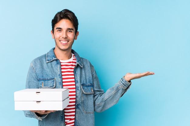 Le giovani pizze caucasiche della tenuta dell'uomo isolate hanno mostrato lo spazio di una copia su una palma e tengono un'altra mano sulla vita.