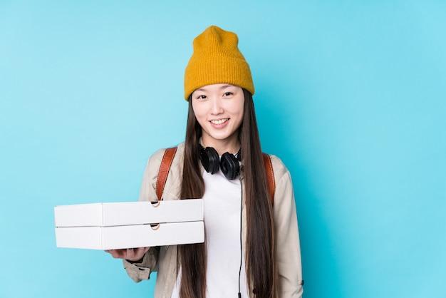 Le giovani pizze cinesi della tenuta della donna hanno isolato felice, sorridendo e allegro.