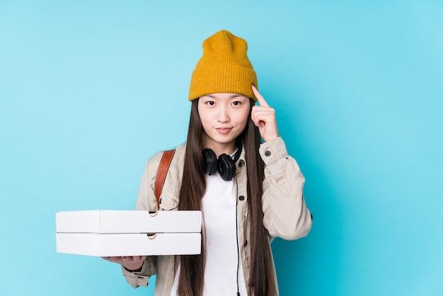 Le giovani pizze cinesi della tenuta della donna hanno isolato il tempio indicante con il dito, pensando, messo a fuoco su un compito.
