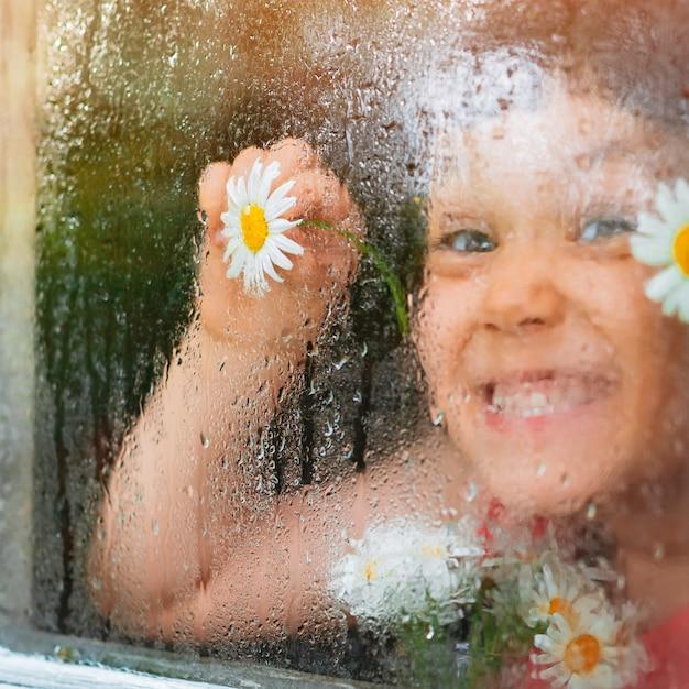 Le gocce di pioggia sul vetro di una finestra del villaggio, gli occhi di fiori di camomilla nelle mani dei bambini guardano la pioggia.