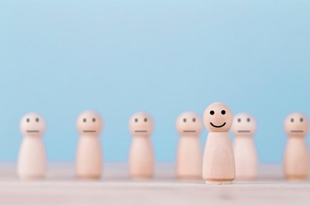 Le icone dell'emoticon di sorriso affrontano il simbolo felice sull'essere umano di legno