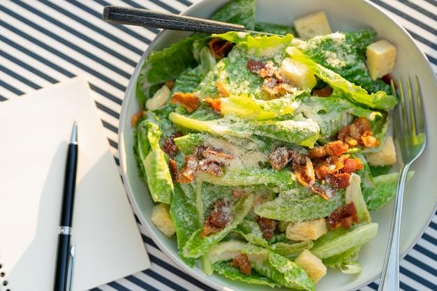Le insalate vengono poste sul tavolo con un quaderno e una penna.