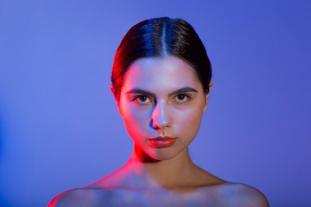 Le labbra rosse del bello giovane ritratto di modello della donna compongono nello studio della luce blu rossa