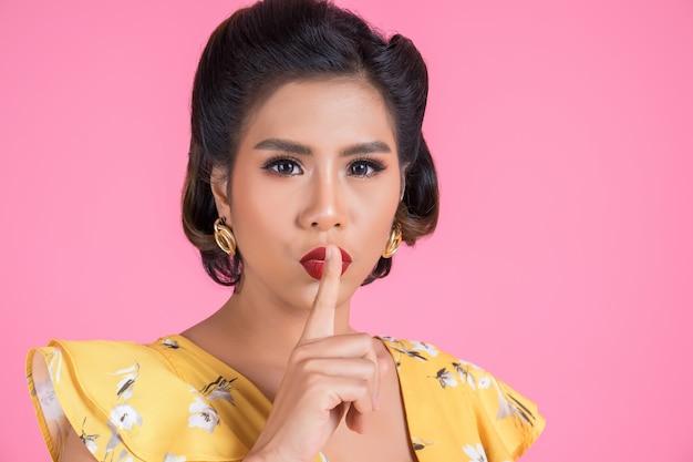 Le labbra rosse e il dito della donna asiatica di bellezza che mostrano il silenzio zittiscono il segno