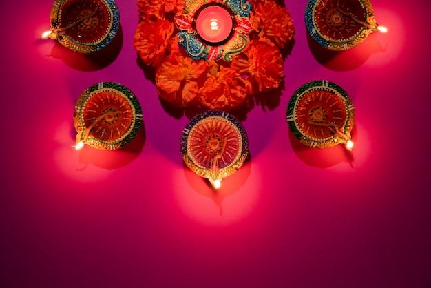 Le lampade clay diya accese durante dipavali celebrano su sfondo rosa