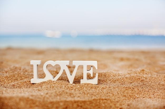 Le lettere di legno amano su una spiaggia sabbiosa che trascura il mare blu