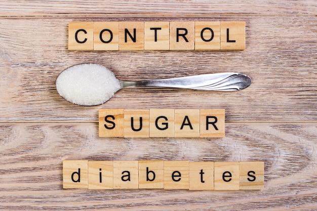 Le lettere di legno del blocco di controllo del diabete e lo zucchero ammucchiano su un cucchiaio