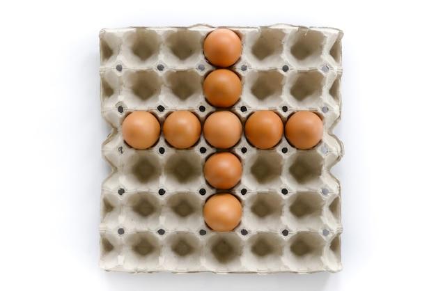 Le lettere di numero organizzano dalle uova in vassoio su fondo bianco.