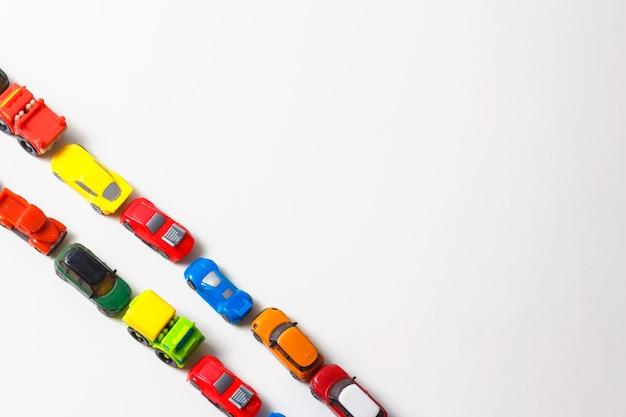 Le macchinine di plastica multicolori sono allineate su bianco