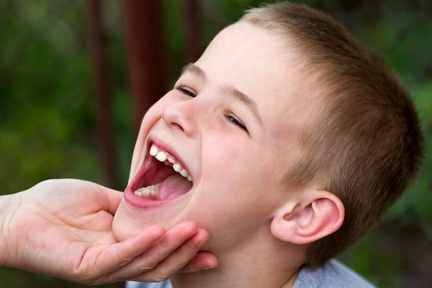 Le madri passano amorevolmente tenendo il mento di piccolo ragazzo bello sorridente che mostra i suoi denti bianchi divertenti del bambino all'aperto su fondo vago.