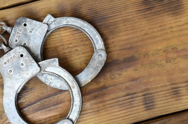 Le manette vecchie e arrugginite della polizia si trovano su una superficie di legno graffiata.