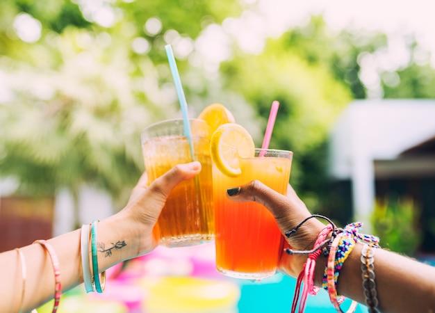 Le mani acclamano il succo del cocktail sulla festa in piscina
