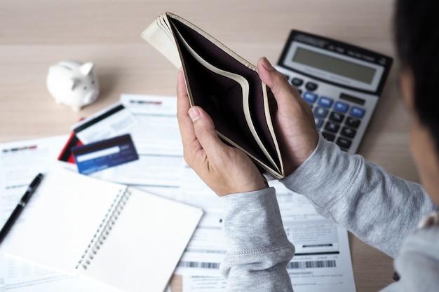 Le mani aprono la borsa vuota dopo aver calcolato il costo dalla carta di credito e fattura. concetto di debito