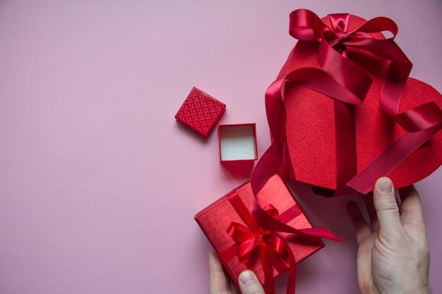 Le mani avvolgono il contenitore di regalo rosso a forma di cuore con il nastro rosso
