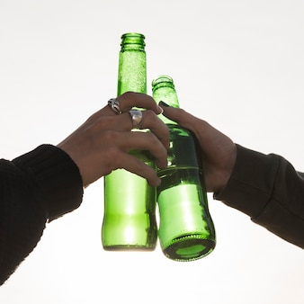 Le mani che rumoreggiavano bottiglie di birra