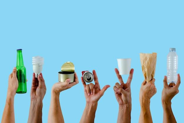 Le mani che tengono e mostrano riciclano i materiali sul blu