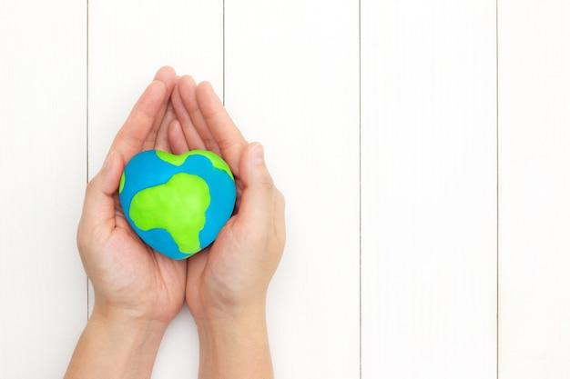 Le mani che tengono il cuore globale modellano sopra fondo di legno bianco con lo spazio della copia.