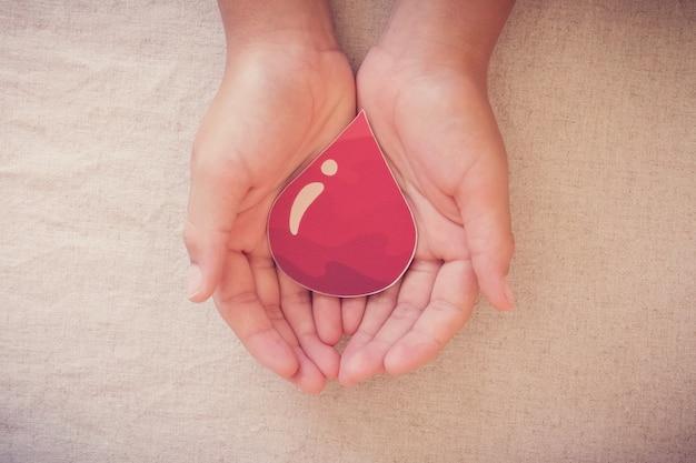 Le mani che tengono la goccia di sangue, danno donazione di sangue, trasfusione di sangue, giornata mondiale del donatore di sangue, concetto di giornata mondiale dell'emofilia