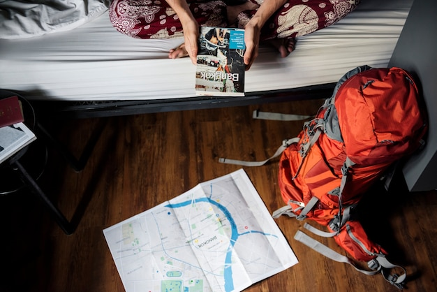 Le mani che tengono la guida di viaggio di bangkok tailandia prenotano con la mappa sul pavimento