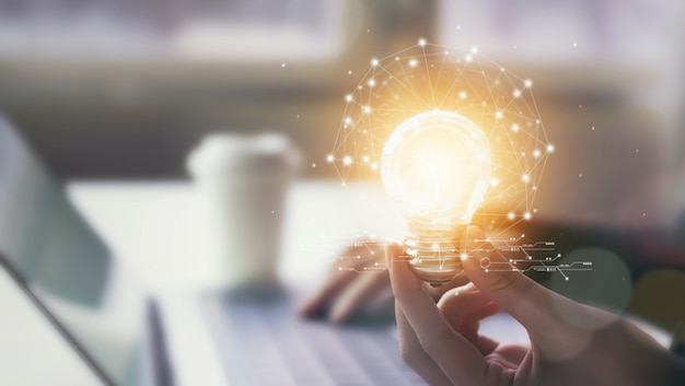 Le mani che tengono la lampadina con innovazione e creatività sono le chiavi del successo.