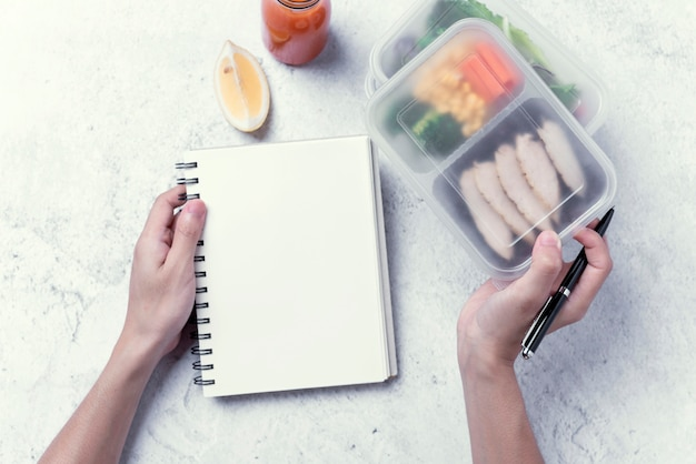 Le mani che tengono la scatola di pranzo sana e il taccuino in bianco per il vostro messaggio di testo o progettazione, ordinano l'alimento.