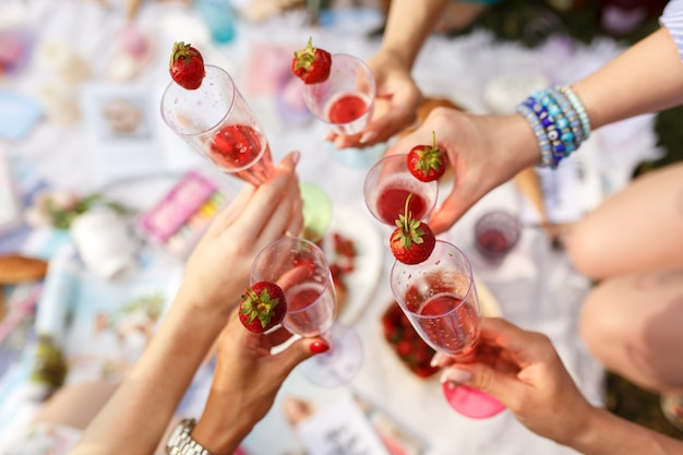 Le mani con i vetri incoraggiano il picnic del giorno di estate.