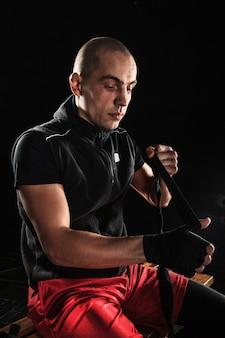 Le mani con la benda di kickboxing di addestramento dell'uomo muscolare sul nero