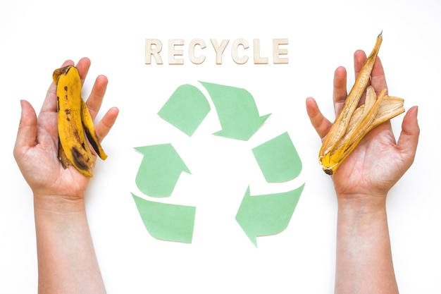 Le mani con rifiuti vicino riciclano la parola e il logo