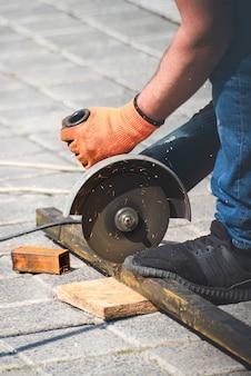 Le mani da lavoro tagliano un tubo di metallo con smerigliatrice angolare