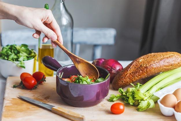 Le mani degli chef preparano un'insalata di ingredienti freschi e sani, verdure e olio d'oliva in cucina