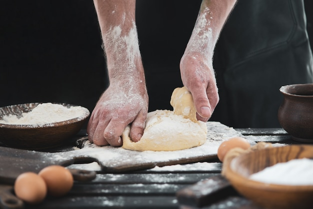 Le mani degli uomini belli e forti impastano l'impasto da cui poi faranno pane, pasta o pizza. una nuvola di farina vola come polvere. accanto all'uovo di gallina