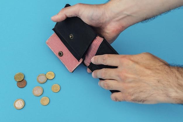 Le mani degli uomini con un primo piano del portafoglio vuoto. euro monete su sfondo blu
