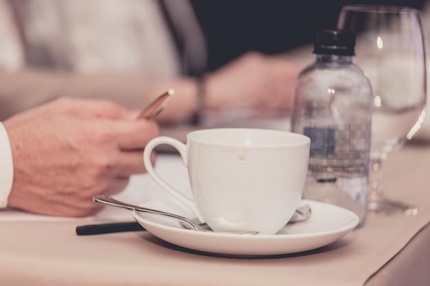Le mani degli uomini d'affari con la penna o la matita, le carte e le tazze di caffè nella stanza di seminario