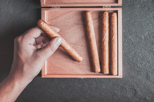 Le mani degli uomini tolgono un sigaro dalla scatola su un tavolo scuro