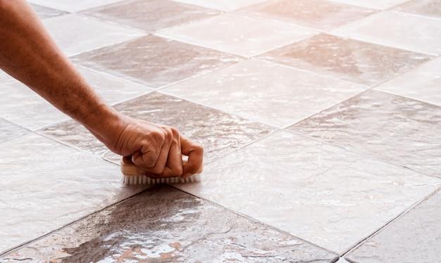 Le mani degli uomini vengono utilizzate per convertire la pulizia della lucidatura sul pavimento piastrellato.