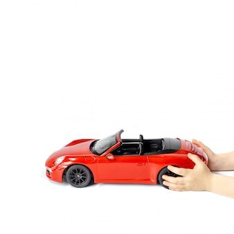 Le mani dei bambini che tengono un'automobile del giocattolo del modello di porsche carrera s 911 di rosso isolata