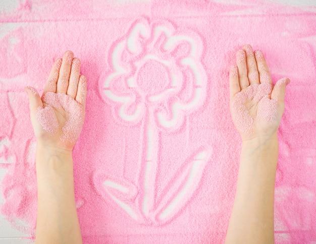Le mani dei bambini creano un fiore decorativo sulla sabbia.