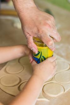 Le mani dei bambini cucinano i cerchi di pasta