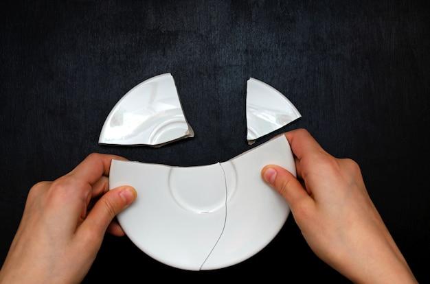 Le mani dei bambini impilano insieme i frammenti di un piatto.