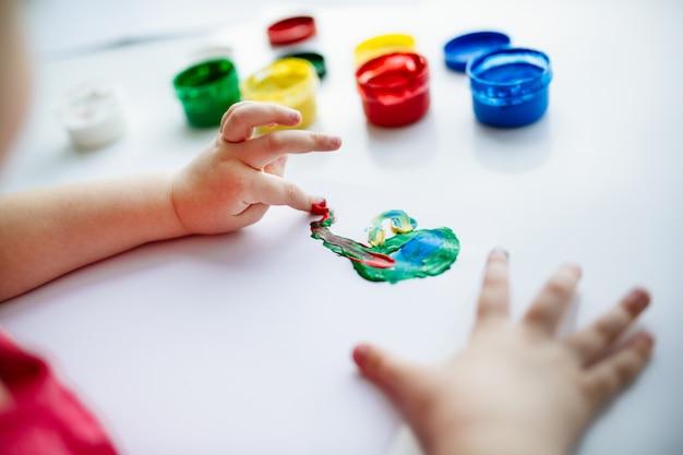 Le mani dei bambini iniziano a dipingere a tavola con le provviste d'arte