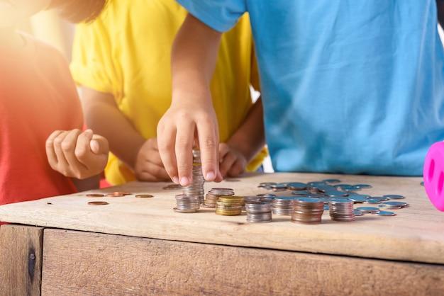 Le mani dei bambini stanno aiutando a mettere le monete nel porcellino salvadanaio isolato su fondo bianco
