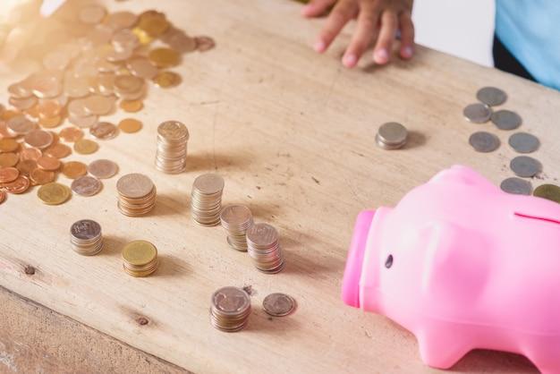 Le mani dei bambini stanno aiutando a mettere le monete nel porcellino salvadanaio su fondo bianco